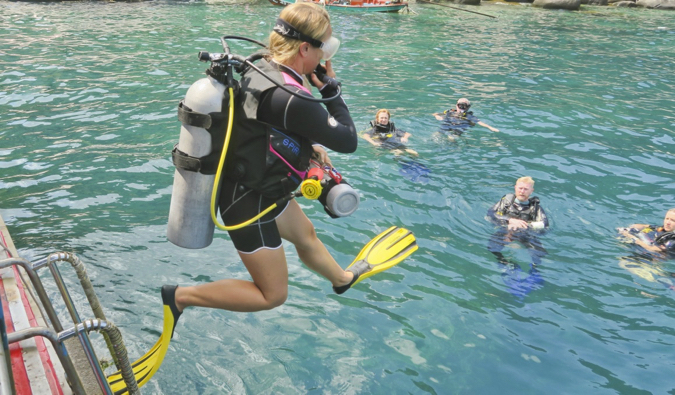 Alex in Wanderland leaping into the water to start a dive in Thailand